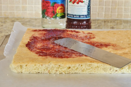 Spread raspberry jam over one layer of almond sponge